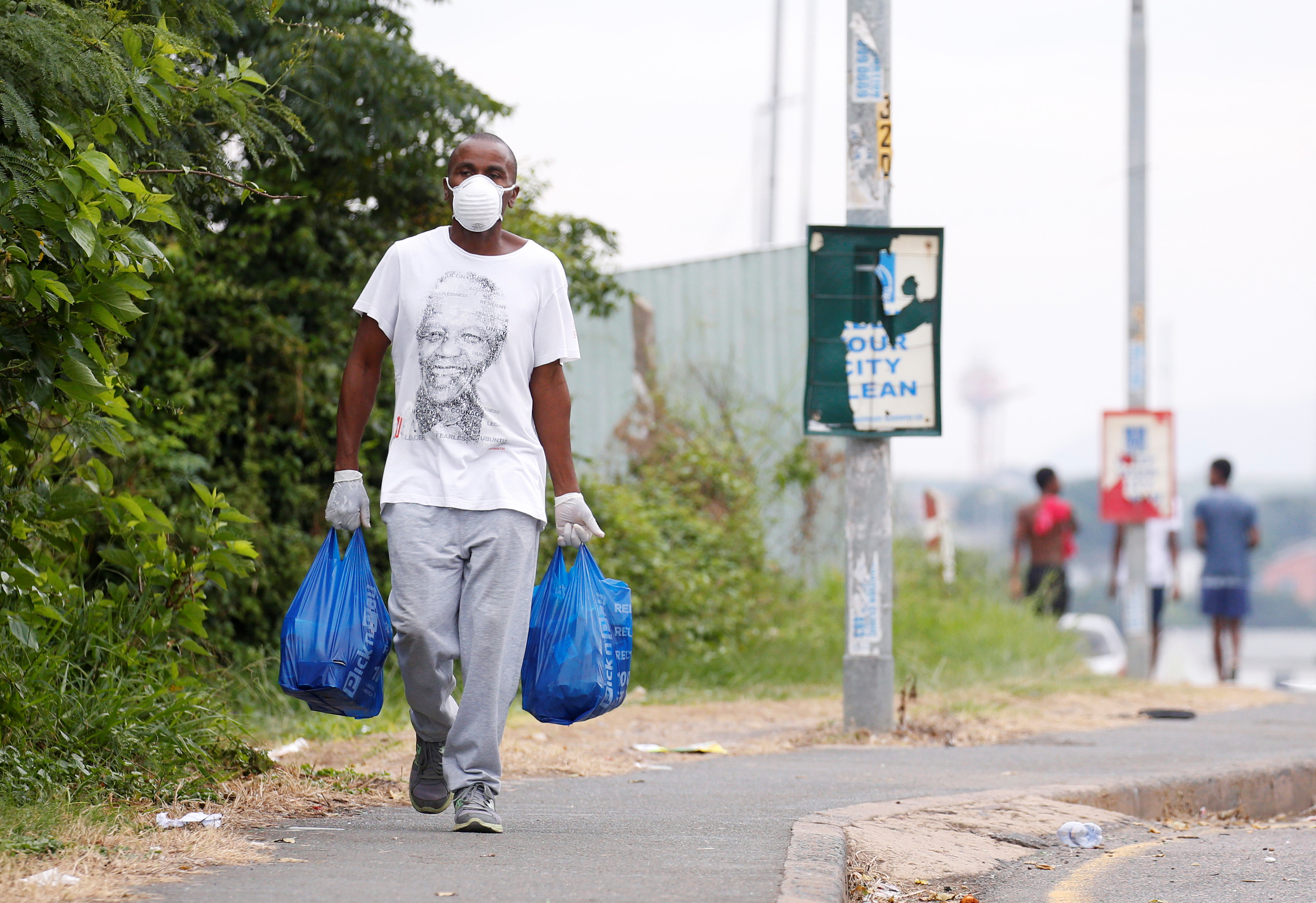 A man carries home groceries during a nationwide 21 day lockdown in an attempt to contain the coronavirus disease (COVID-19) outbreak in Umlazi township near Durban